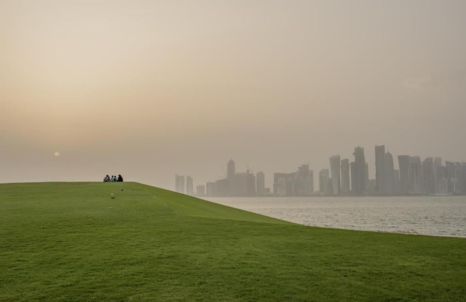 Migrants in a park at sunset in Doha, Qatar, July 15, 2017. In recent decades, Doha has transformed into a gleaming metropolis of global ambition, but assertions that it is furthering dissent and terrorism have led to a blockade form four of its fellow Arab states. (Tomas Munita/The New York Times)