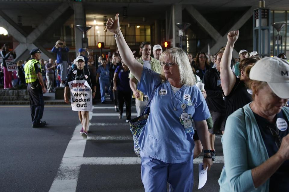 Tufts nurse Cathy Murray gaved a thumbs up as she and other nurses head back to work after a one-day strike followed by a lockout.