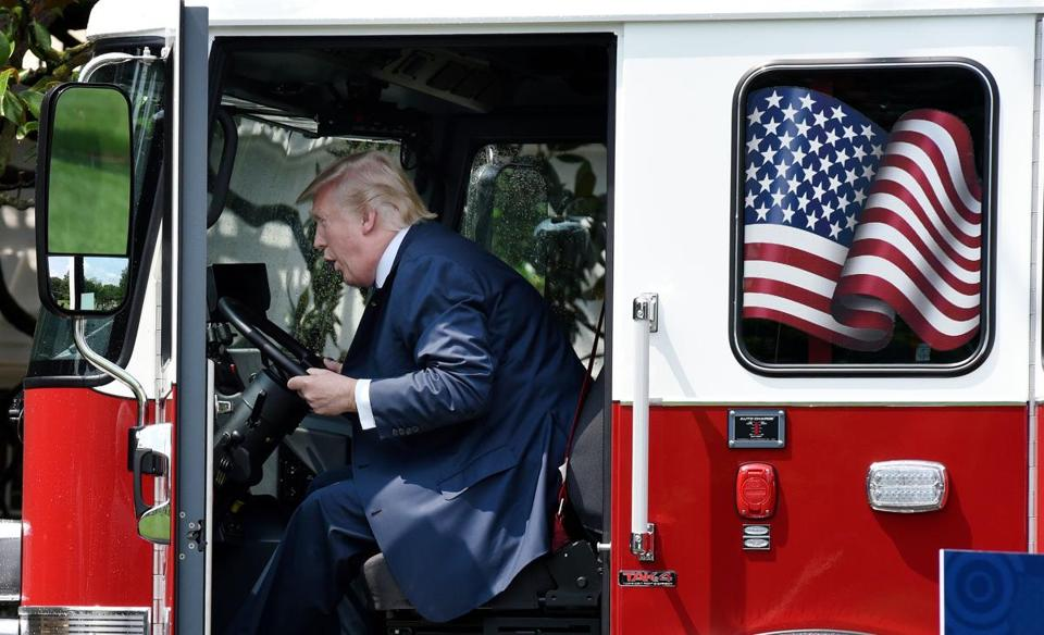 "President Donald Trump examines a fire truck from Wisconsin-based manufacturer Pierce on the South Lawn during a ""Made in America"" product showcase event at the White House in Washington, DC, on July 17, 2017. / AFP PHOTO / Olivier DoulieryOLIVIER DOULIERY/AFP/Getty Images"