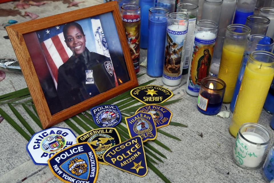 Various police department badges were placed at a sidewalk memorial for New York Police officer Miosotis Familia in New York.