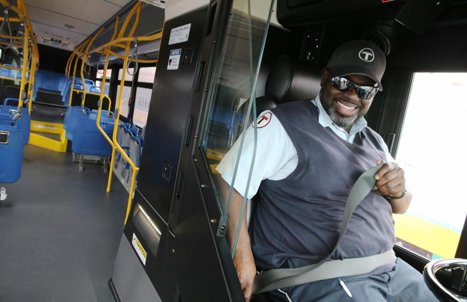 Boston, MA- July 18, 2017: Bus operator Daron Banks buckles his seatbelt before moving a compressed natural-gas bus being displayed by the MBTA/MassDOT in Boston, MA on July 18, 2017. The nearly $290 million investment includes 156 diesel-electric hybrid buses, 175 compressed natural-gas (CNG) buses, and 44 sixty-foot, articulated buses, helping to replace the entire fleet of Silver Line vehicles serving the busy Washington Street corridor between Roxbury and downtown Boston. (CRAIG F. WALKER/GLOBE STAFF) section: regional reporter: