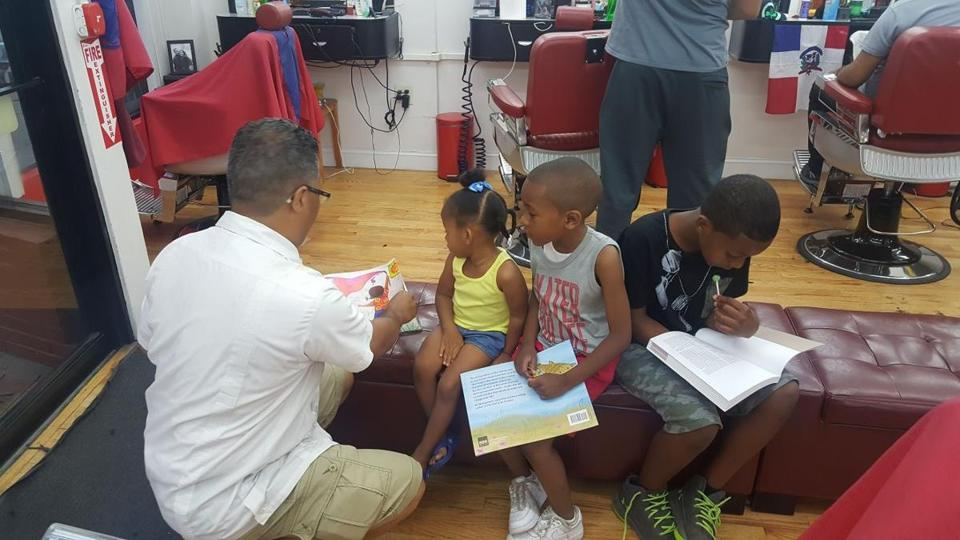 Kids at Micky's Barbershop in Egleston Square take home a free book as part of the Books at the Barbershop program.