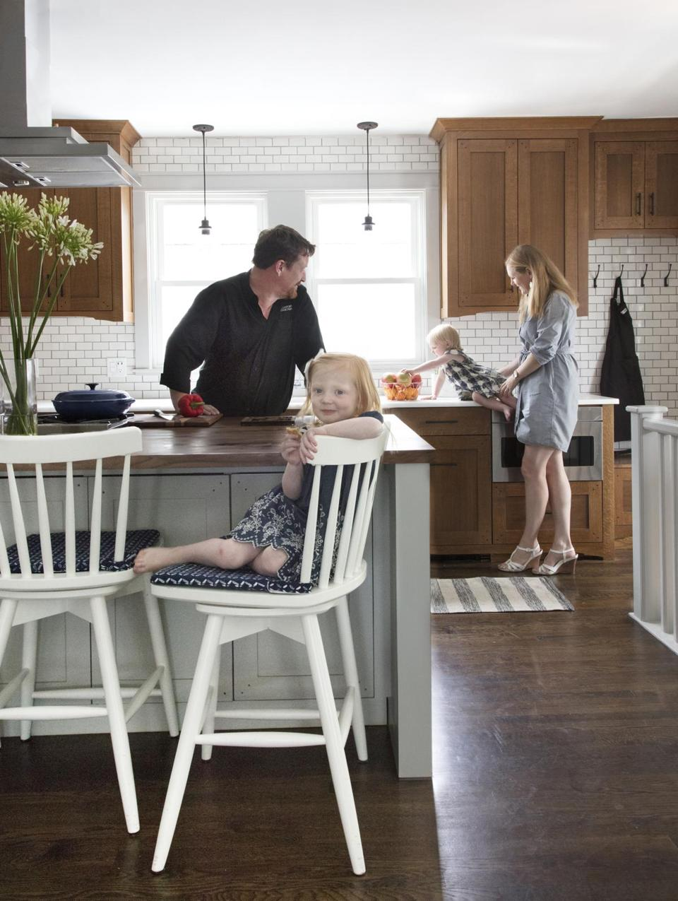 "Jim, Georgia, Mairead, and Emily Burke in their updated kitchen. The Mission-style cabinets are fumed oak; the island top is walnut. Counters are ""white rhino"" quartzite. The backsplash is made of Heath Ceramics tiles, ""in a combination of matte and glossy finishes,"" says interior designer Sarah Scales."
