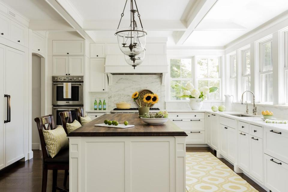 Pendants above the island are fitted with hand-forged iron, and the cabinet hardware is solid bronze.