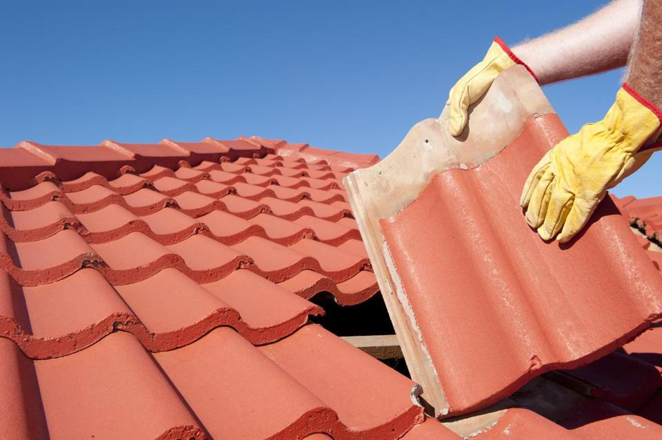 Roof repairs worker with yellow gloves replacing red tiles or shingles on house with blue & Replace your roof? Patch it? Wait a year? Hereu0027s how to decide ... memphite.com