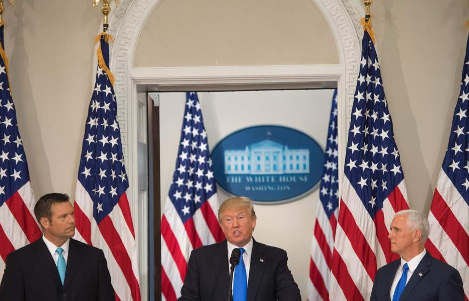 President Donald Trump spoke alongside Kansas Secretary of State Kris Kobach, left, and Vice President Mike Pence , right, during the first meeting of the Presidential Advisory Commission on Election Integrity.