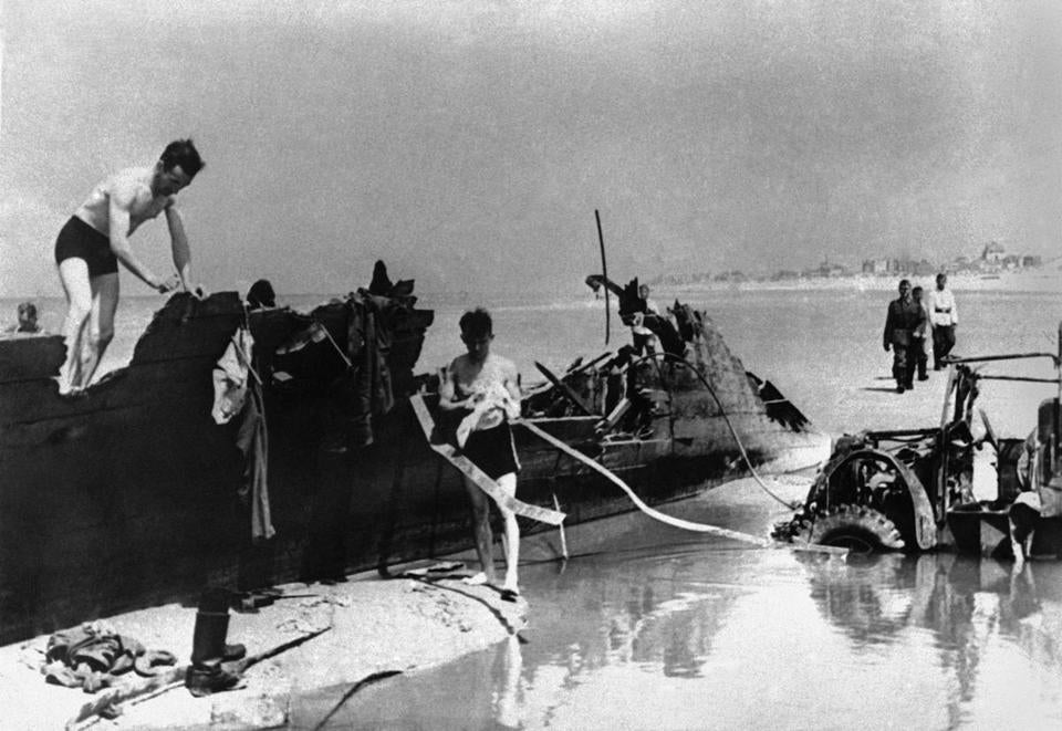 These German troops are bathing on the beach of Dunkerque on July 27, 1940, amid the mementoes left by the fleeing British and French troops who managed to escape the Flanders trap which developed when the Nazi columns smashed through the French line north of the Maginot line.