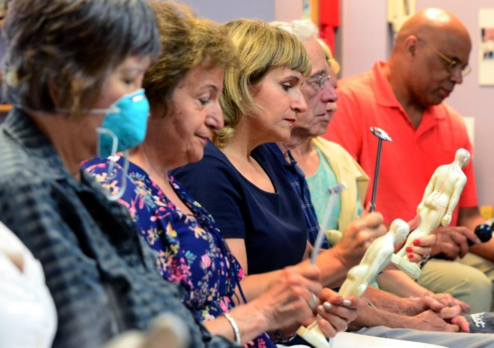 Quincy 07/19/2017: At the Oriental Culture Institute in Quincy , a large group of people gathered for Tom Tam's Healing class. (l-r) Carol Huang, Georgia Contes, Julie Kalustian, Richard O'Connor and Chuck Christain tap on the acupuncture dolls with a metal hammer, calling out letters and numbers for the pathways associated with specific organs of the human body that is imprinted on the human figure model. Photo by Debee Tlumacki for the Boston Globe (south)
