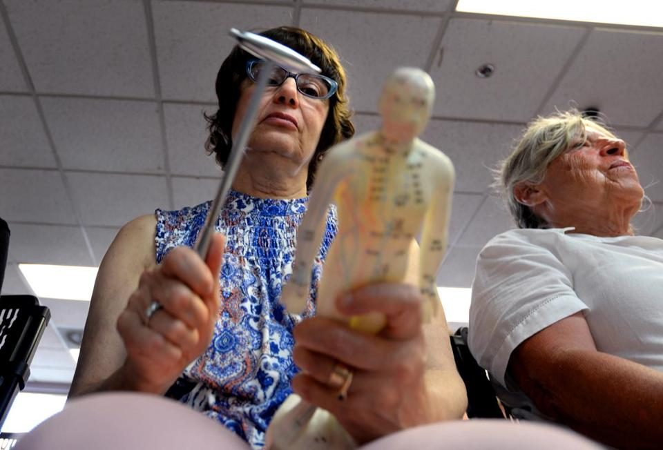 Quincy 07/19/2017: At the Oriental Culture Institute in Quincy , a large group of people gathered for Tom Tam's Healing class. Elaine Harmon from Hyde Park, taps on an acupuncture doll with a metal hammer, calling out letters and numbers for the pathways associated with specific organs of the human body that is imprinted on the human figure model. Photo by Debee Tlumacki for the Boston Globe (south)