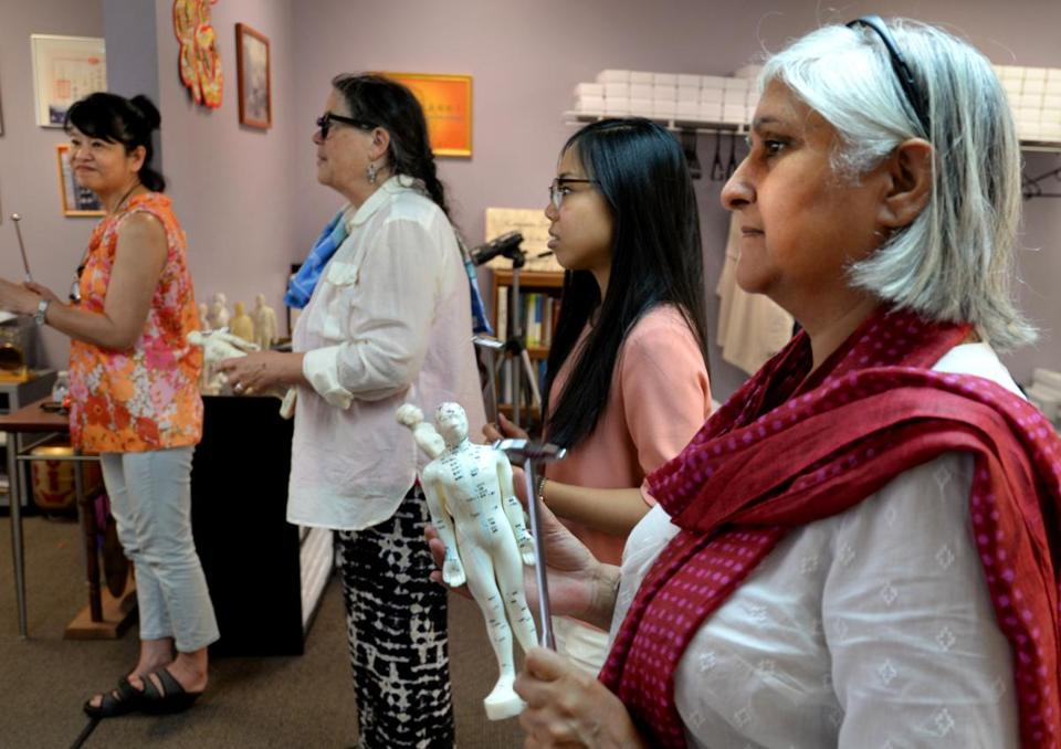 Quincy 07/19/2017: At the Oriental Culture Institute in Quincy , a large group of people gathered for Tom Tam's Healing class. Healer Hardeep Mann (cq) (far right) taps on a acupuncture doll with a metal hammer along with others. They tap on letters and numbers for the pathways associated with specific organs of the human body that is imprinted on the human figure model. Photo by Debee Tlumacki for the Boston Globe (south)