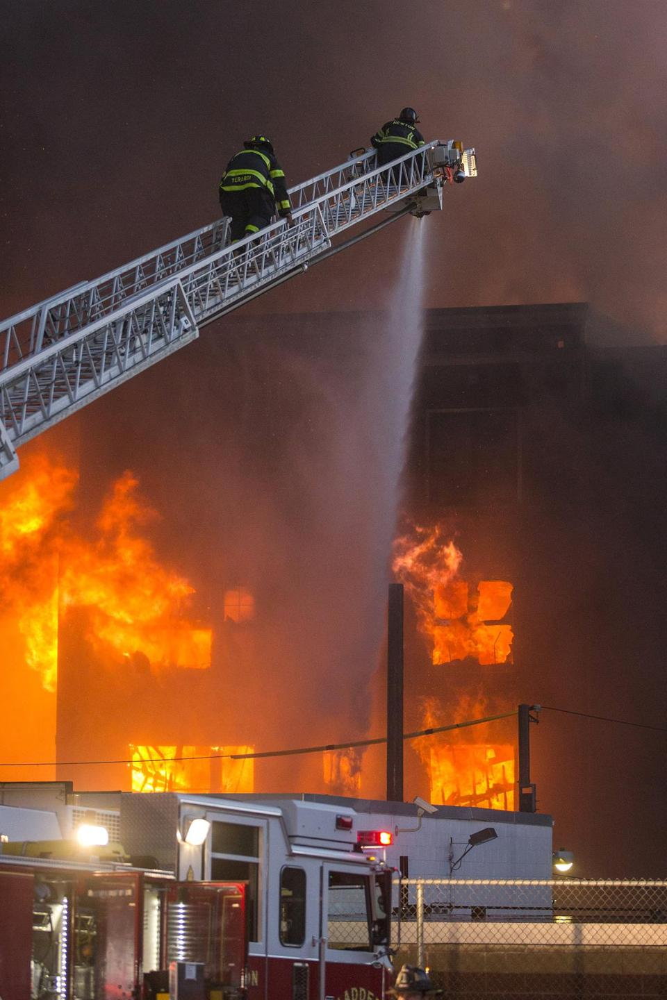 Firefighters put water on a fully involved building at the scene of an 8 alarm fire in Waltham on Sunday, July 23, 2017 that involved multiple structures. (Scott Eisen for The Boston Globe)
