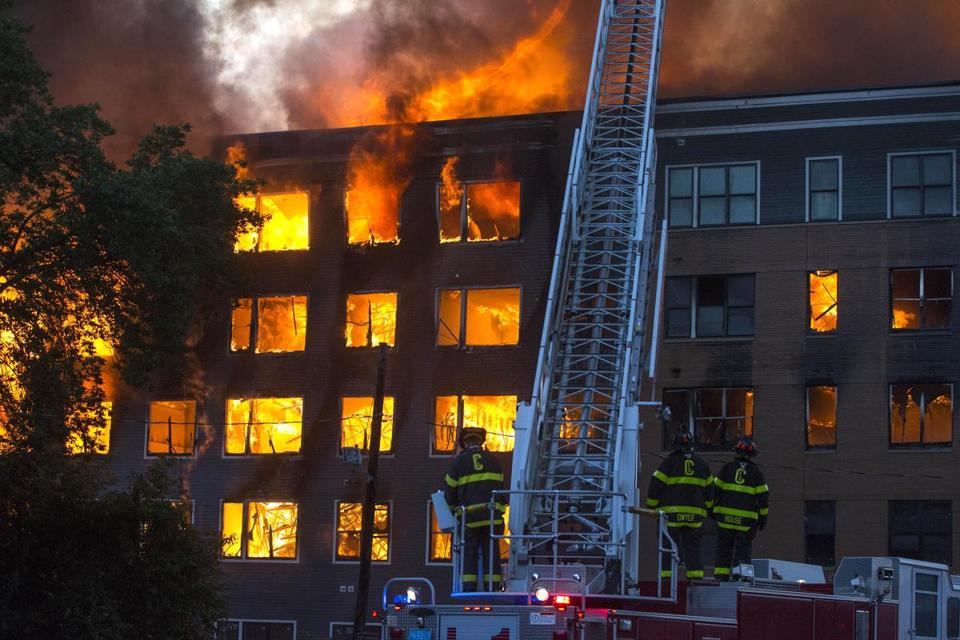 Brookline firefighters watched as fire and smoke poured from a building.