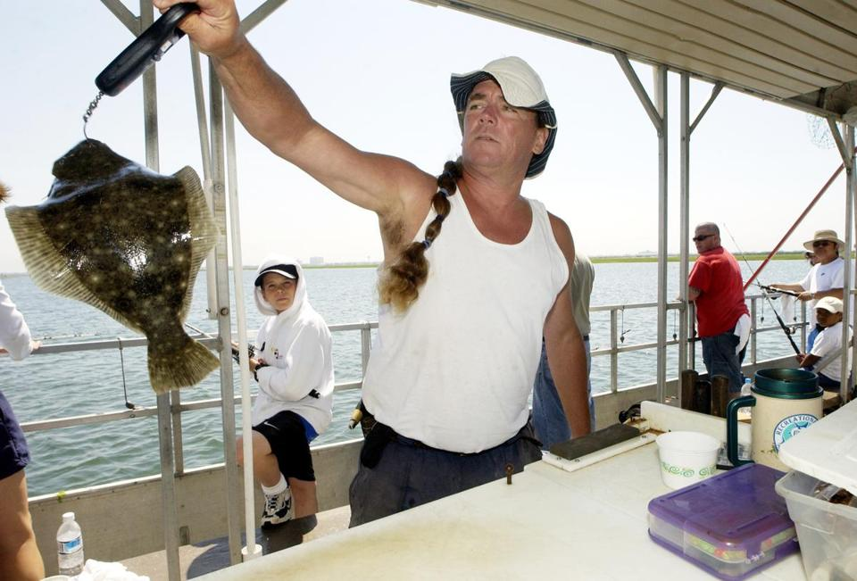 First mate Michael Mulveen weighed a fish aboard the Duke O'Fluke fishing boat during an outing in the Great Egg Harbor Bay near Somers Point, N.J.