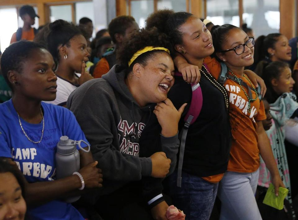 Long Island, MA -- 7/27/2017 - (L-R:) Damaris Sweeney, 21, of Milton, watches the slideshow as her fellow group leader Paige Belfield, 20, of Boston sings along to the song playing and serenades to her campers Maya Thompson, 16, of Dorchester and Lesley Pires, 13, of Brockton at Camp Harbor View on Long Island. (Jessica Rinaldi/Globe Staff) Topic: 29campharborview Reporter: