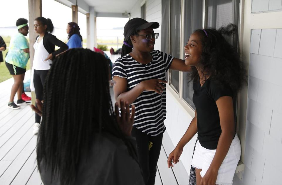 Long Island, MA -- 7/27/2017 - (L-R) Krystal Gentle, 11, of Roxbury looks on as Natalia Edwards, 12, of Jamaica Plain places Sadie Metellus, 11, of Boston in front of the fan so her hair can blow in the wind at Camp Harbor View on Long Island. (Jessica Rinaldi/Globe Staff) Topic: 29campharborview Reporter:
