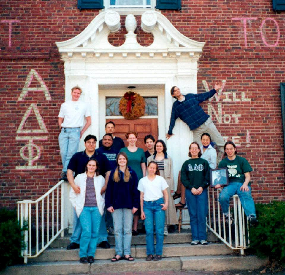 A photo of the Bowdoin Alpha Delta Phi members for the 1998 college yearbook. Thomas Clark is seen standing on the railing on the left.