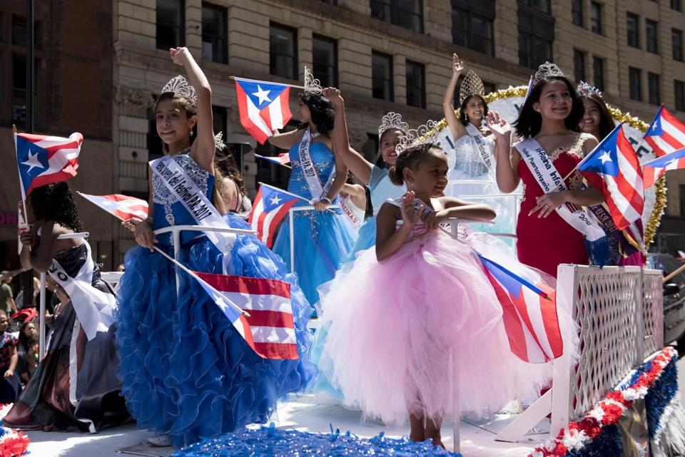 Past and current Puerto Rican Festival Queens rode a float on Sunday.