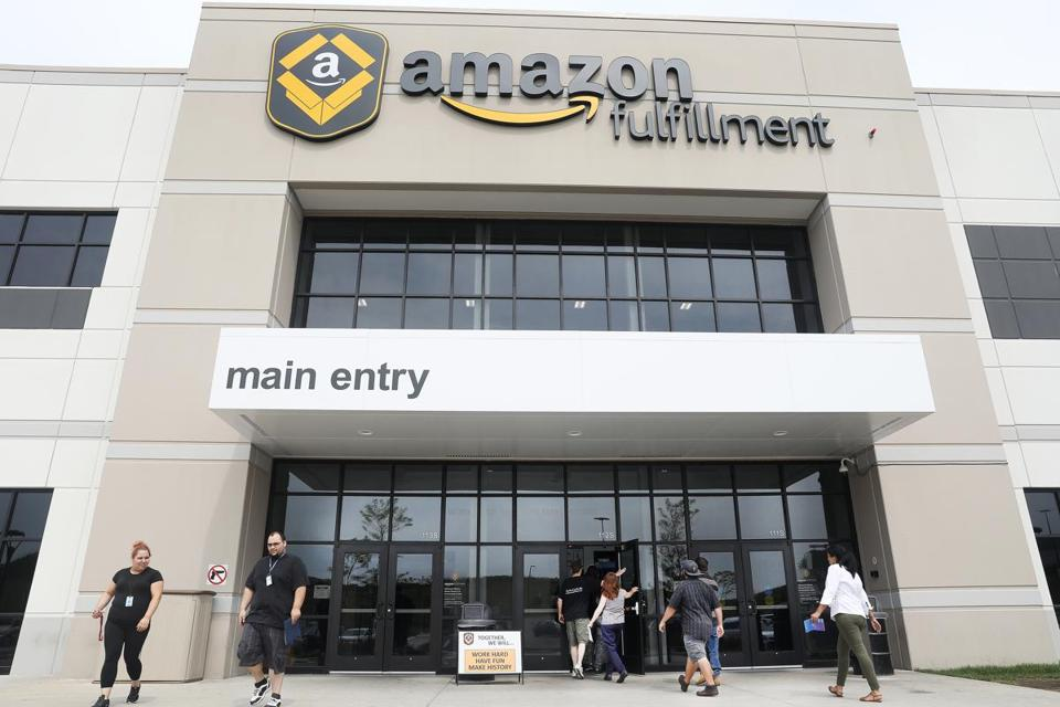 A group of job applicants, right, started a tour at Amazon fulfillment center in Fall River.