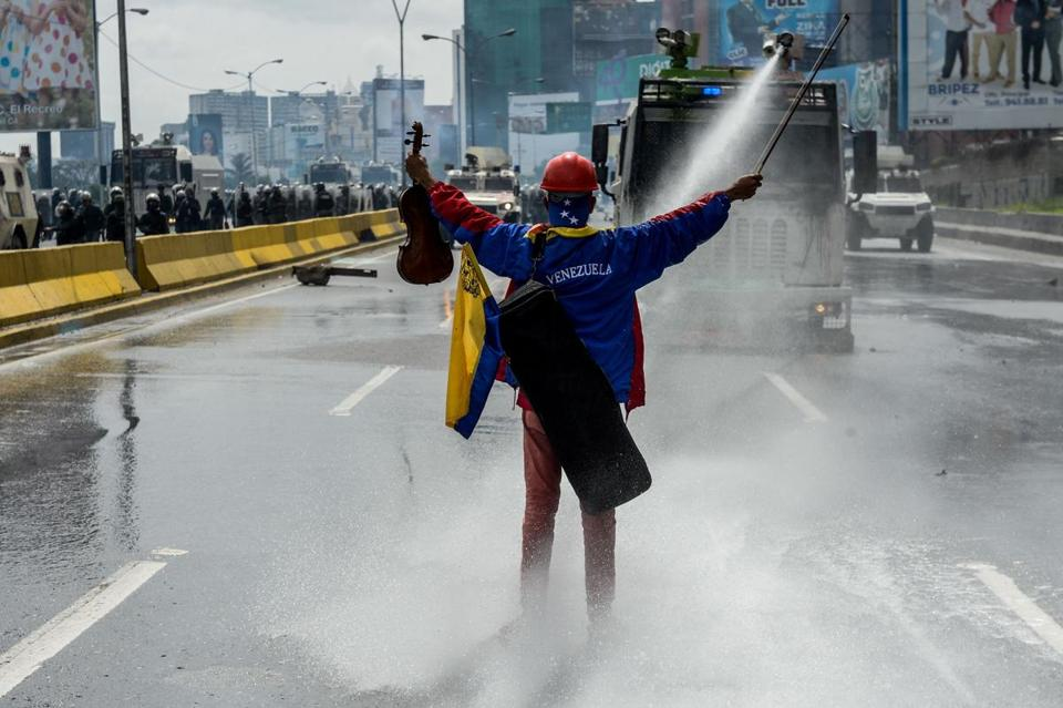 (FILES) This file photo taken on May 24, 2017 shows opposition activist and violin player Wuilly Arteaga in front of an armoured vehicle of the riot police during a protest against President Nicolas Maduro in Caracas. According to a human rights NGO report, Artega, 23, was arrested on July 27, 2017, during a protest within a 48-hour strike called by the opposition. / AFP PHOTO / FEDERICO PARRAFEDERICO PARRA/AFP/Getty Images