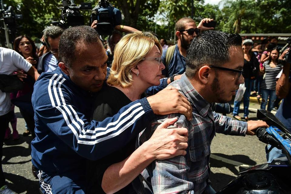 Attorney general Luisa Ortega (center) is driven away after being kept out of her office in Caracas by the National Guard.