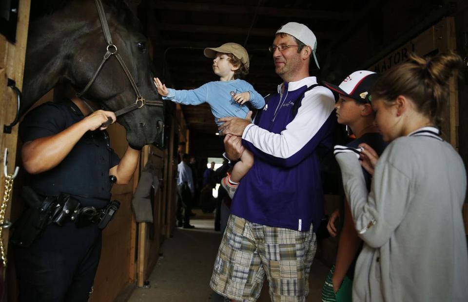 Kevin Shea, 2, reached out to pet Midnight, a Mounted Patrol Unit horse, as his dad, Kevin, held him and his brother Brady, 11, and sister Ireland, 8, watched Tuesday.