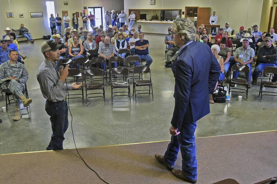 Riley Schriefer, left, asks a question of Gov. Doug Burgum at a town hall meeting in Golden Valley, N.D., in July.