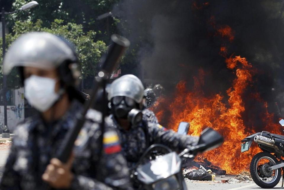In this Sunday, July 30, 2017 photo, Bolivarian National Guards move away from the flames after an explosion in Altamira Plaza during clashes with anti-government demonstrators in Caracas, Venezuela. The explosion injured several officers and damaged several of their motorcycles. The officers were then seen throwing several privately owned motorcycles into the remaining fire in reprisal. (AP Photo/Ariana Cubillos)