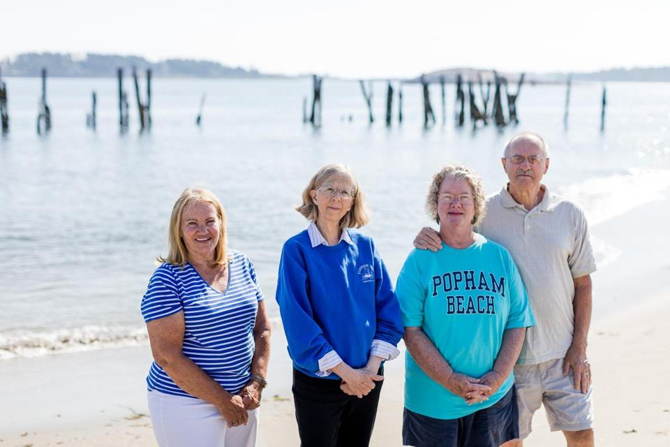 Phippsburg, ME, United States -- Homeowners in favor of preserving rotting wharf pilings against the wishes of a contractor who wants them removed, from left, Mary McNamara, Ellen Louise Hart, Jackie Gallo and Jim Gallo stand in front of the pilings off of Popham Beach in Phippsburg, ME on Thursday, August 10, 2017. The state has approved their removal but the town has filed an appeal to save the historic pilings which were part of a wharf in the 19th century for steamships. (Yoon S. Byun for the Boston Globe) Slug: 11popham Reporter: Brian Macquarrie LOID: 8.3.3350342101