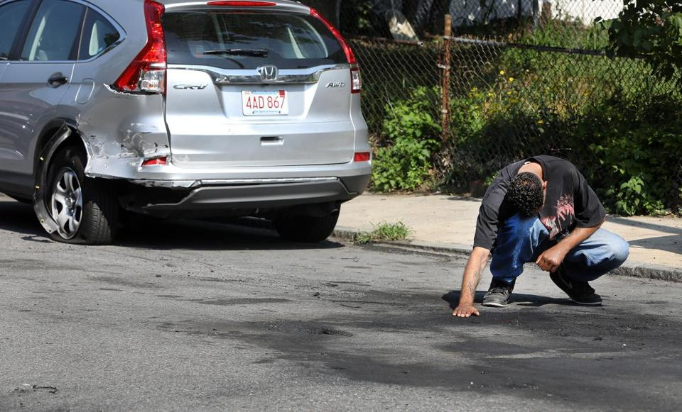 An unidentified man placed his hand where two people were killed after gunshots were fired and a car crashed in Dorchester on Thursday.