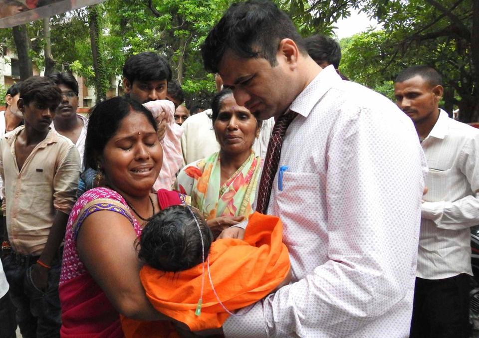 An Indian woman carries a child at the Baba Raghav Das Hospital in Gorakhpur, India.