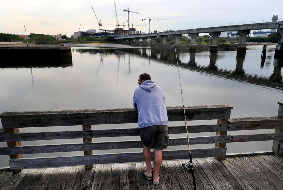Somerville-8/12/17- A man fishes from a pier on the Mystic River behind Assembly Row near where the contruction on the new Wynn Casio takes place across the water in Everett. The Amelia Earhart Dam is to the left and the MBTA bridge spans the river to the right. A new pedestrian and bike bridge is proposed somewhere to cross the river close to this location. John Tlumacki/Globe Staff(metro)
