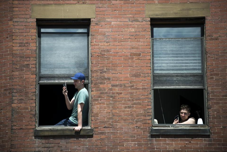 Boston, MA - 8/13/17 - Residents film the parade from windows during the Dominican Parade down Centre St on Sunday, August 13, 2017. (Nicholas Pfosi for The Boston Globe) Topic: 14parade(2)