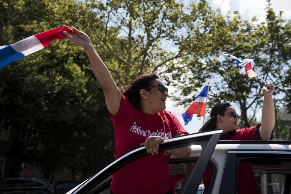 Two participants cheered and waved flags during the Dominican Festival parade.