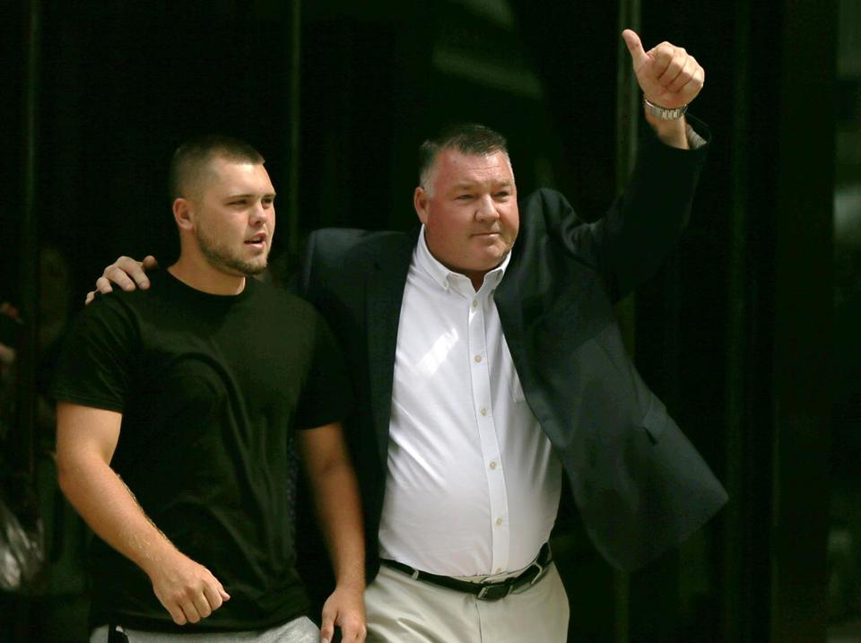 Defendant John Fidler (right) gave a thumbs-up as he left the John Joseph Moakley Courthouse.