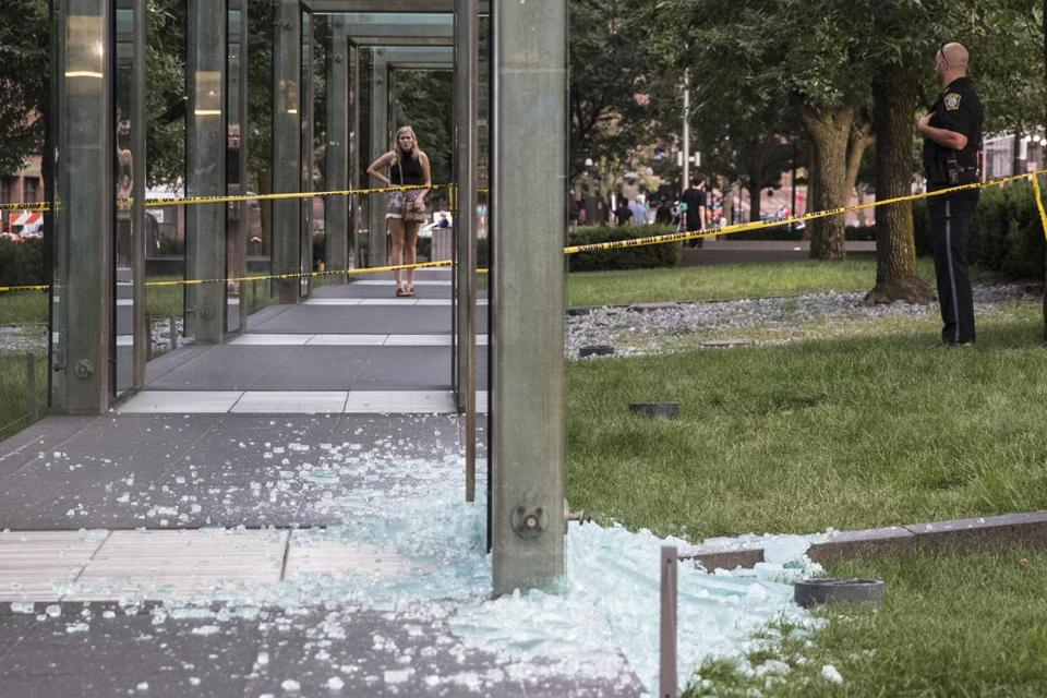 Investigators looked at glass sitting on the ground after it was vandalized.