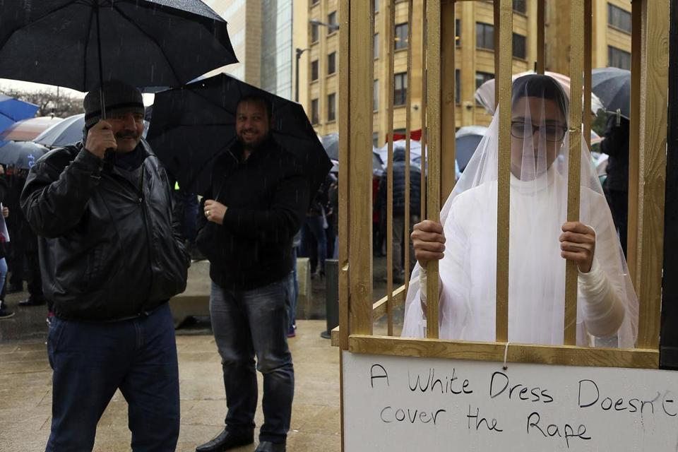 "FILE -- In this March 15, 2017 file photo, an activist from the Lebanese NGO Abaad stands in a golden cage dressed as a bride while during a protest in front of the government building in downtown Beirut, Lebanon. On Wednesday Aug. 16, 2017, Parliament repealed a law that allowed rapists to avoid prison by marrying their victims, which had been in place since the 1940s, and follows years of campaigning by women's rights advocates. Tunisia, Morocco and Egypt have canceled similar ""marry the rapist"" clauses over the years, and Jordan's parliament recently repealed a similar law. (AP Photo/Hassan Ammar, File)"