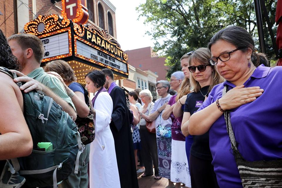 CHARLOTTESVILLE, VA - AUGUST 16: Clergy observe a moment of silence during the memorial service for Heather Heyer outside the Paramount Theater August 16, 2017 in Charlottesville, Virginia. The memorial service was held four days after Heyer was killed when a participant in a white nationalist, neo-Nazi rally allegedly drove his car into the crowd of people demonstrating against the 'alt-right' gathering. (Photo by Chip Somodevilla/Getty Images)