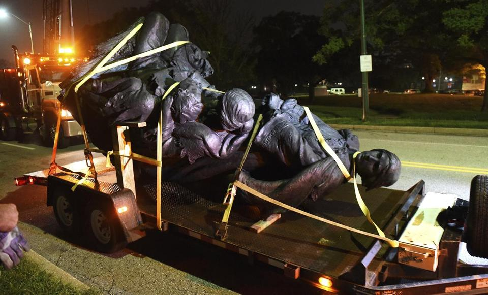 A monument dedicated to the Confederate Women of Maryland lies on a flatbed trailer early Wednesday, Aug. 16, 2017, after it was taken down in Baltimore. Local news outlets reported that workers hauled several monuments away early Wednesday, days after a white nationalist rally in Virginia turned deadly. (Jerry Jackson/The Baltimore Sun via AP)