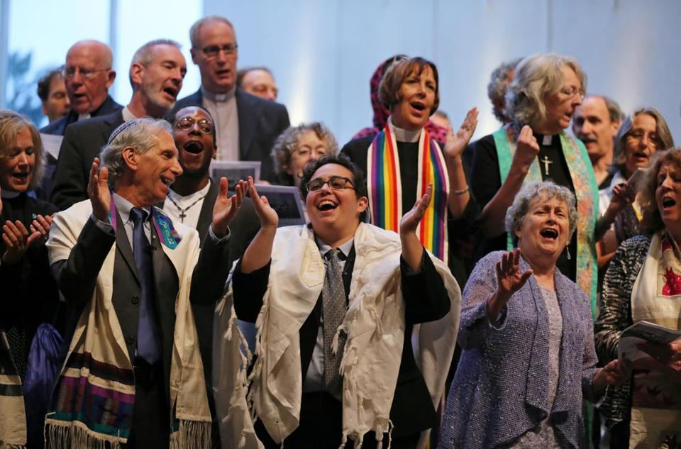 "Boston, MA- August 18, 2017: Religious leaders took to the stage for the closing song, ""This Land Is Your Land,"" during the Interfaith Gathering of Unity, Love, and Strength at Temple Israel of Boston in Boston, MA on August 18, 2017. Organized by the Greater Boston Interfaith Organization, the gathering offered an opportunity to come together and send a message of unity and diversity in the face of hate. Thousands of protesters are expected to flood downtown Boston Saturday, with a pro-free speech rally on Boston Common likely surrounded by several different counter-actions. (CRAIG F. WALKER/GLOBE STAFF) section: metro reporter:"