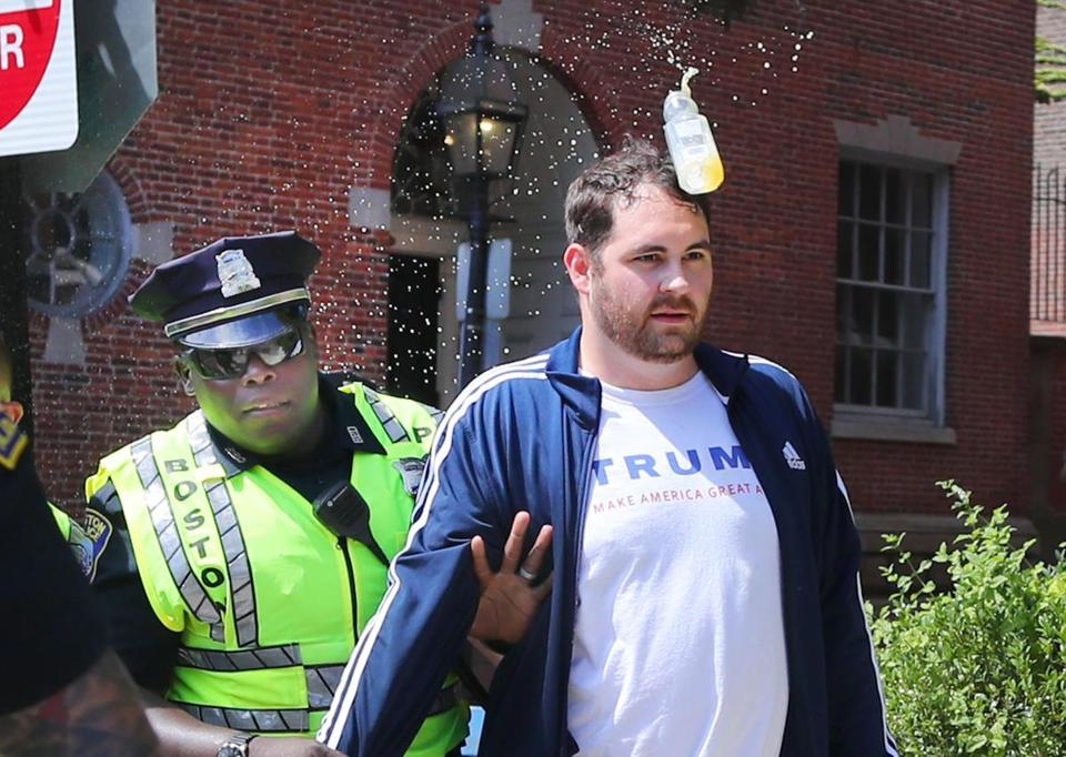 "A police officer escorted a participant in Saturday's ""free speech"" rally away from the scene as a water bottle was headed in his direction."