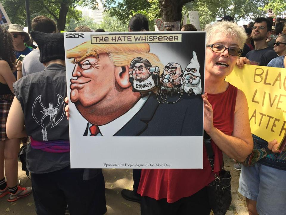 A woman held up a sign about President Donald Trump.