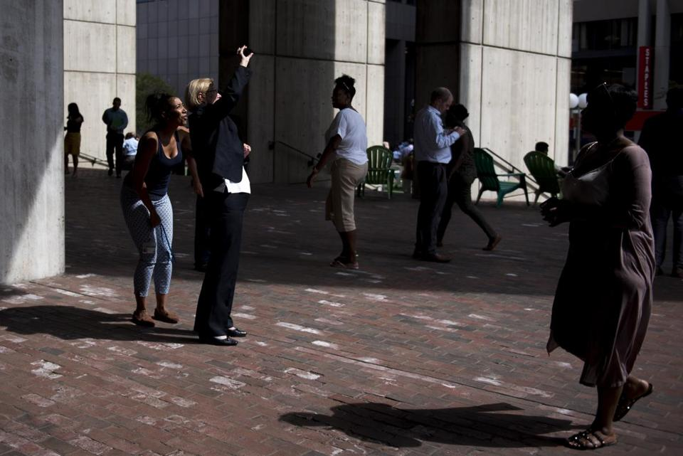 Sally Glora, center, and Teki,, left, check out the sun during the partial solar eclipse in City Hall Plaza.