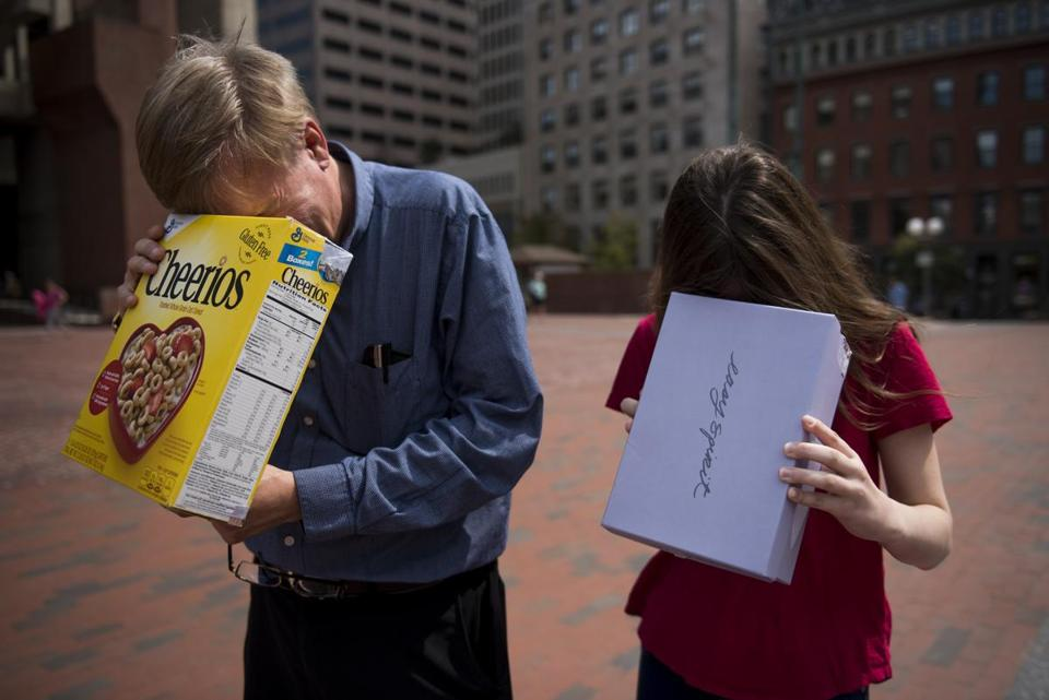 Mike Wilson, left, and his daughter Stephanie, check out the partial solar eclipse in City Hall Plaza.