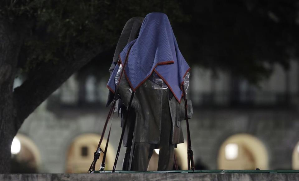 Confederate statutes removed from the University of Texas's campus in Austin were secured to a trailer early Monday.