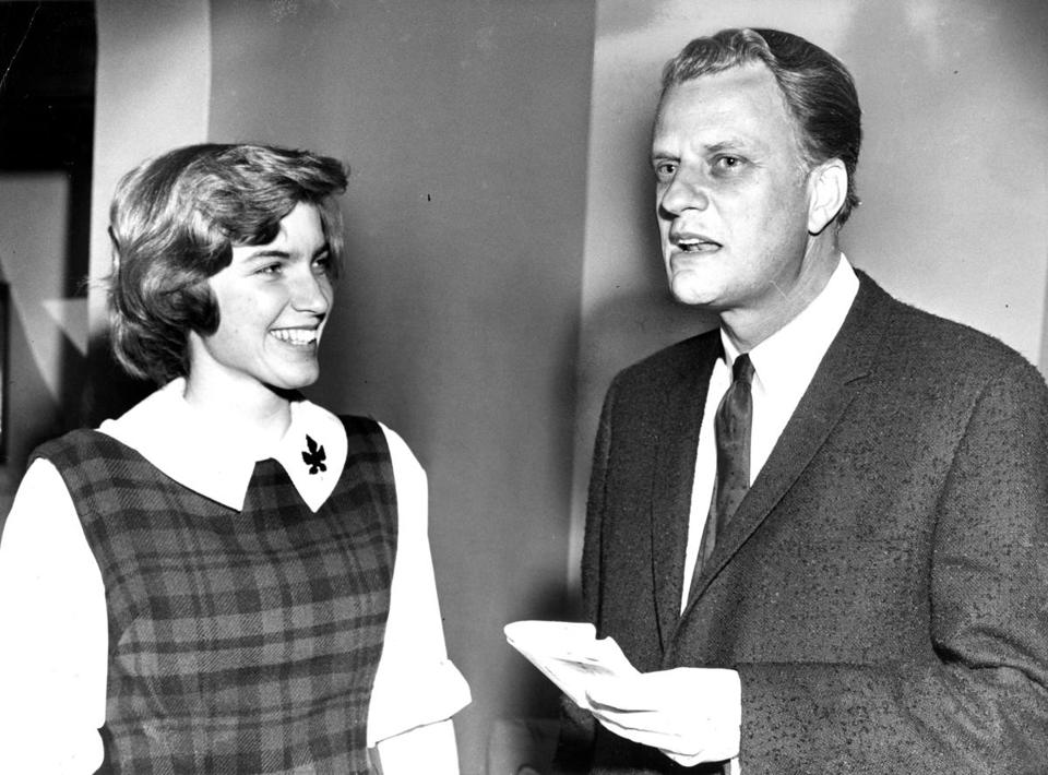 Evangelist Billy Graham with Betsy Loutrel of Cincinnati, OH, chairman of a meeting sponsored by the Wellesley Christian Fellowship at Wellesley College in Wellesley, MA on Feb. 17, 1964.