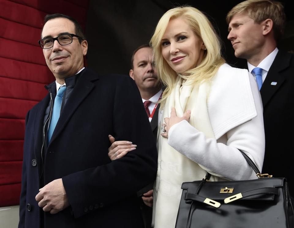 "FILE - In this Friday, Jan. 20, 2017, file photo, then Treasury Secretary-designate Stephen Mnuchin and his then-fiancee, Louise Linton, arrive on Capitol Hill in Washington, for the presidential inauguration of Donald Trump. Linton offered a condescending response to a social media critic on Aug. 21, 2017, telling a mother of three that that she was ""adorably out of touch."" Mnuchin and Linton were married in June. (Saul Loeb/Pool Photo via AP, File)"