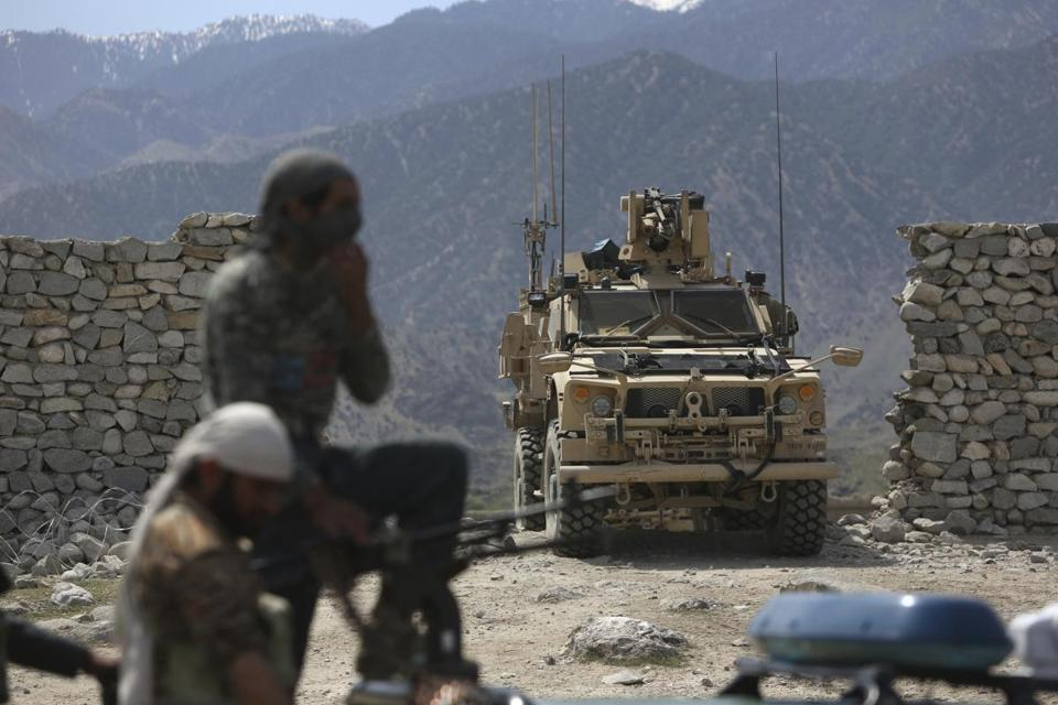 "FILE - In this April 17, 2017 file photo, U.S. forces and Afghan security police are seen in Asad Khil near the site of a U.S. bombing in the Achin district of Jalalabad, east of Kabul, Afghanistan. Behind the detail-scarce rhetoric of the new Afghanistan strategy, elements of President Donald Trump's broader approach to foreign conflicts emerge: secret military plans, no ""nation-building"" and a reliance on regional players to squeeze wayward nations and extremist groups. (AP Photo/Rahmat Gul, File)"