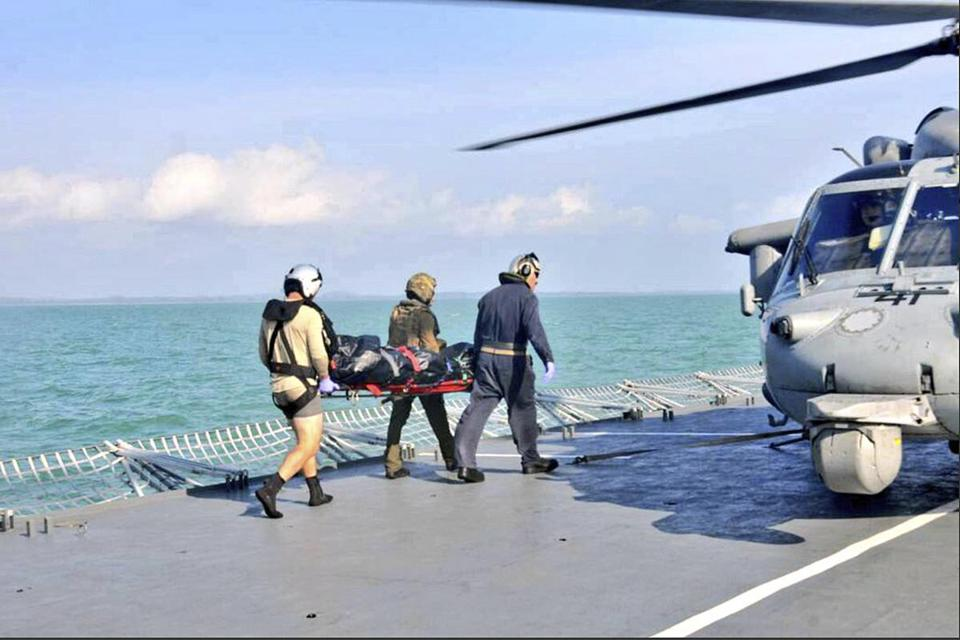 A body recovered by the Royal Malaysian Navy is taken Wednesday to a US Navy helicopter off the Malaysian coast.