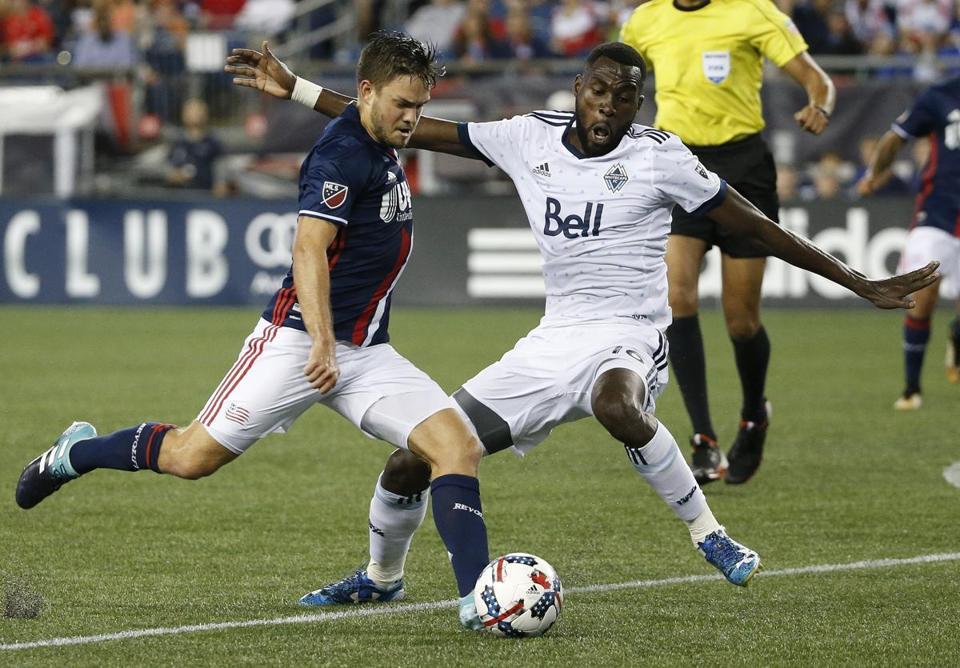 Vancouver Whitecaps' Tony Tchani, right, defends against New England Revolution's Kelyn Rowe during the second half of an MLS soccer game, Saturday, Aug. 12, 2017, in Foxborough, Mass. (AP Photo/Michael Dwyer)