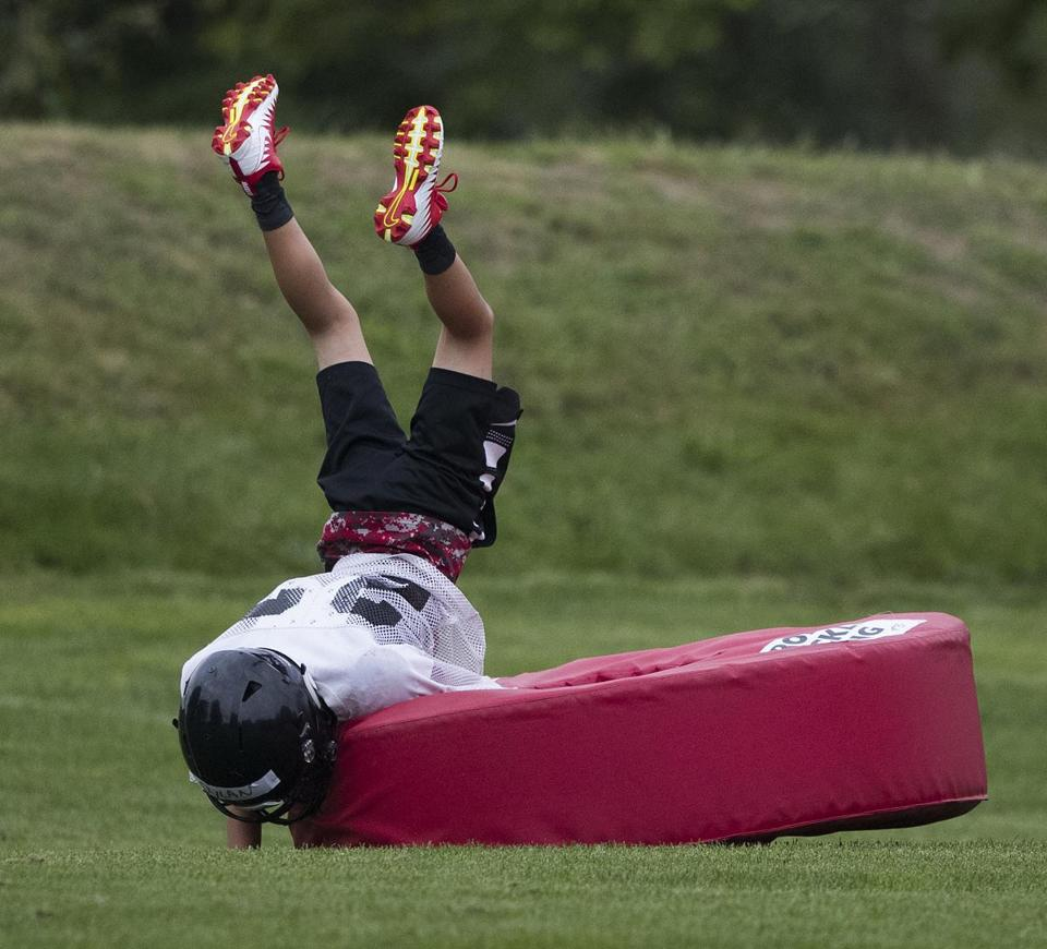 A Wellesley player hits a tackling dummy in practice.